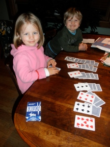 Mimi has learned how to play solitaire. Orin helps.